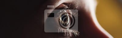 Naklejka close up view of human eye looking away in darkness, panoramic shot