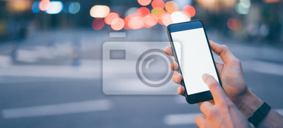 Naklejka Closeup image of male hand holding smartphone with blank screen. Mockup ready for text message or content. Man's hands with cellphone. Empty display. Night street, bokeh light
