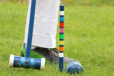 Closeup of a croquet ball next to a mallet, the post, and a person's leg