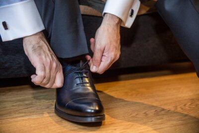Naklejka Closeup shot of a man tying his shoelaces