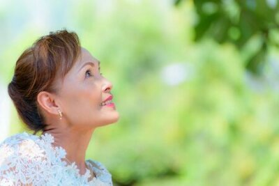 Naklejka Closeup side face of a healthy Asian middle-aged woman dress in Thai style clothes, Portrait old lady resting outdoors looking up smiling happy in the park, copy space on green tree nature background