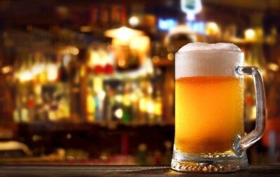 Naklejka cold mug of beer in a bar on wooden table