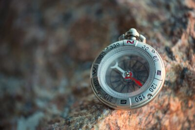 Compass on the beach. Tourist equipment as a background..
