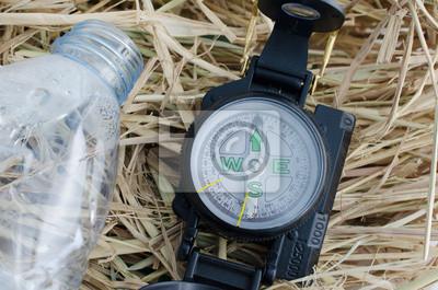 compass z pustą butelką wody na sianie
