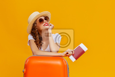 Naklejka concept of travel. happy woman girl with suitcase and  passport on  yellow background.