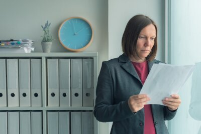 Naklejka Concerned businesswoman reading business report papers in office