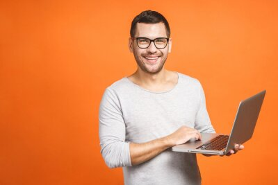 Naklejka Confident business expert. Confident young handsome man in casual holding laptop and smiling while standing against orange background.
