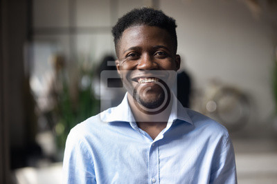 Naklejka Confident smiling young african businessman looking at camera in office