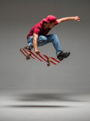 Naklejka Cool young guy skateboarder jumps on skateboard in studio on grey background. Photography about skateboarding tricks