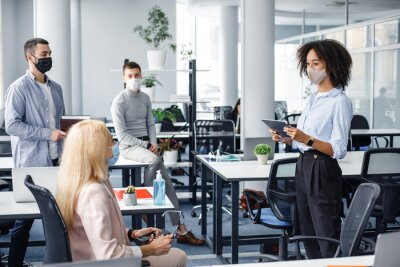 Naklejka Corporate meeting and group work in company. African american woman manager in protective mask holding tablet, talking to workers keeping social distance