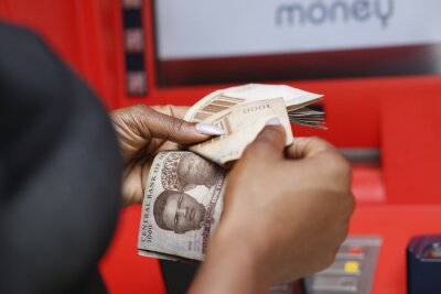 Naklejka Counting Naira notes in front of an ATM