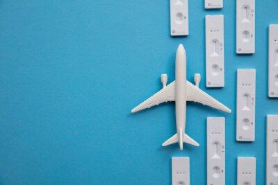 Naklejka Covid travel concept. Airplane with covid19 antigen test kits