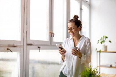 Naklejka Creative business woman using smartphone in loft office