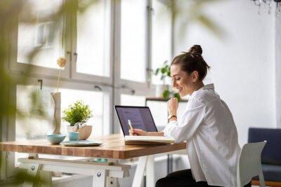 Naklejka Creative young woman working on laptop in her studio