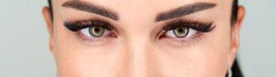 Naklejka Cropped female face with long eyelashes closeup