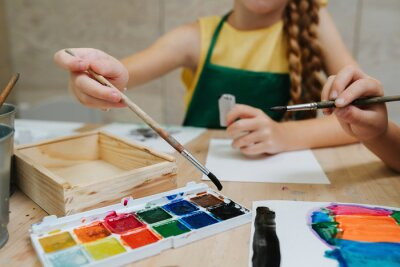 Naklejka Cropped image of kids painting with watercolor. Low angle.