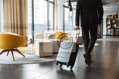 Naklejka Cropped photo of caucasian businessman wearing suit walking with suitcase in hotel lobby