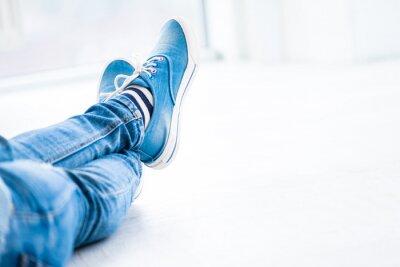 Naklejka Crossed legs wearing gumshoes on white background