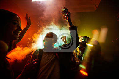 Naklejka Crowd of cheerful hilarious young multiethnic people drinking alcohol and dancing in smoke at noisy party