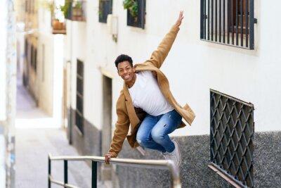 Naklejka Cuban man jumping for joy over a handrail in the street.