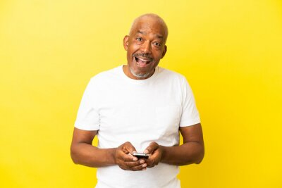 Naklejka Cuban Senior isolated on yellow background surprised and sending a message
