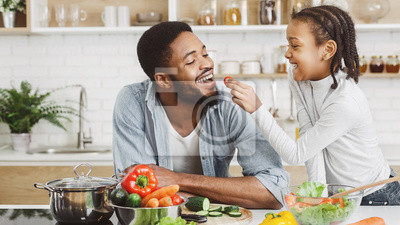 Naklejka Cute african girl giving her dad cherry tomato while cooking