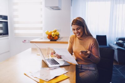 Naklejka Cute caucasian smiling blonde woman in sweater holding bills in one hand and in other smart phone. On table are laptop and bills. Apartment interior.