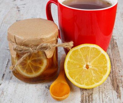 Naklejka Cytryna z miodem i filiżanka herbaty na drewnianym stole, zdrowe odżywianie