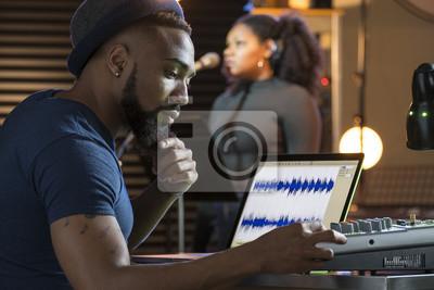 Naklejka Czarna wokalistka pracująca z inżynierem dźwięku w studio nagrań