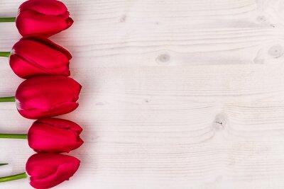 Naklejka Czerwone tulipany na jasnym drewnie z wolnego miejsca na tekst