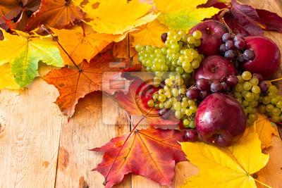 Czerwoni soczyści Dojrzali jabłka z winogronami i jesień liśćmi klonowymi na drewnianym tle