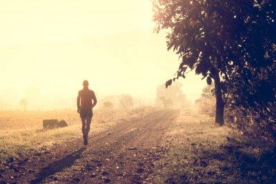 Naklejka Człowiek działa na ścieżce w lesie