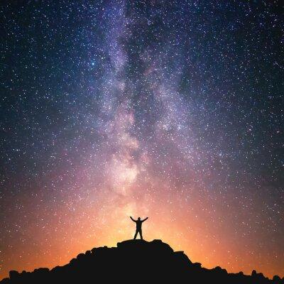 Naklejka Człowiek i Wszechświat. Człowiek stoi na szczycie wzgórza obok Drogi Mlecznej z rękami podniesione do powietrza.