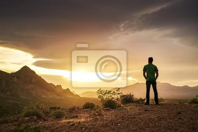 Naklejka człowiek ogląda złoty zachód słońca nad górami w pustyni nevada