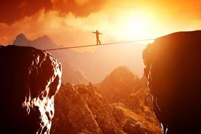 Naklejka Człowiek spaceru i balansowanie na linie nad przepaścią w górach