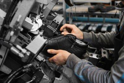 Naklejka Człowiek używa specjalnej obrabiarki do robienia butów. Przenośnik w fabryce butów z butem i podeszwą. Masowa produkcja obuwia.