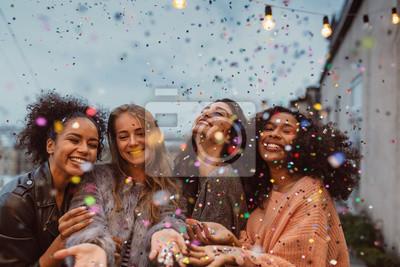 Naklejka Cztery piękne kobiety stojące na tarasie pod konfetti.