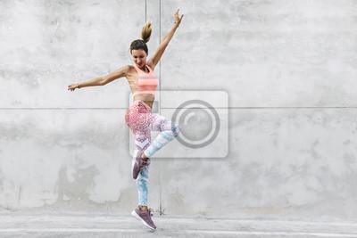 Naklejka Dancer in fashion sportswear jumping over gray wall
