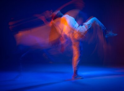 Naklejka Dancing sportive female in colorful neon light. Expressive contemporary dance. Studio photography with long exposure
