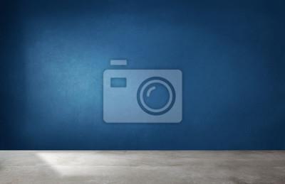 Naklejka Dark blue wall in an empty room with a concrete floor