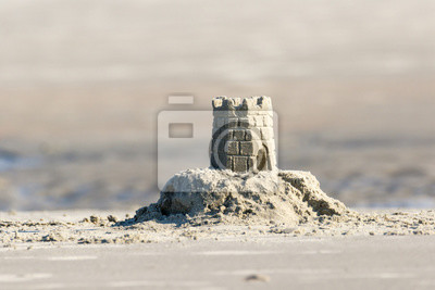 Naklejka Detailed sand castle on the beach with a tidal pool in the background