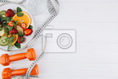 Naklejka Diet plan, menu or program, tape measure, water, dumbbells and diet food of fresh fruits on white background, weight loss and detox concept, top view
