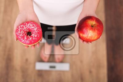 Naklejka Dieta. Kobieta pomiaru ciała ciężar na ważenie skali gospodarstwa Donut i jabłko. Słodycze są niezdrowe Junk Food. Diety, zdrowe odżywianie, styl życia. Utrata masy ciała. Otyłość. Widok z góry
