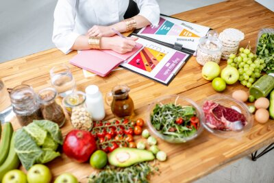 Naklejka Dietetyk pisze plan diety, widok z góry na stole z różnymi zdrowymi produktami i rysunki na temat zdrowego odżywiania