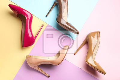 Naklejka Different stylish high heeled shoes on color background
