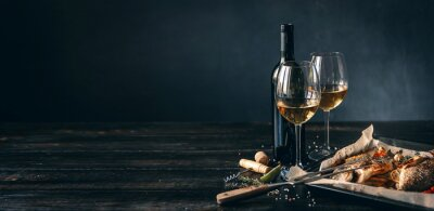 Naklejka dinner concept for two. two glasses of white wine, baked fish.
