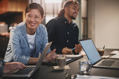 Naklejka Diverse businesspeople smiling while working with colleagues in