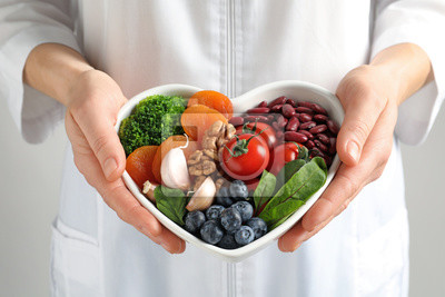 Naklejka Doctor holding bowl with products for heart-healthy diet, closeup