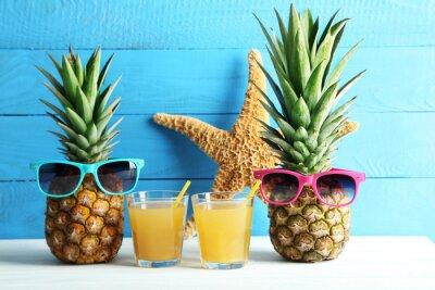 Naklejka Dojrzałe ananasy z szklanki soku na białym drewnianym stole