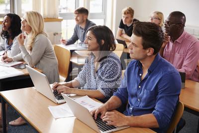 Naklejka Dojrzali uczniowie siedzący przy biurkach w klasie edukacji dorosłych